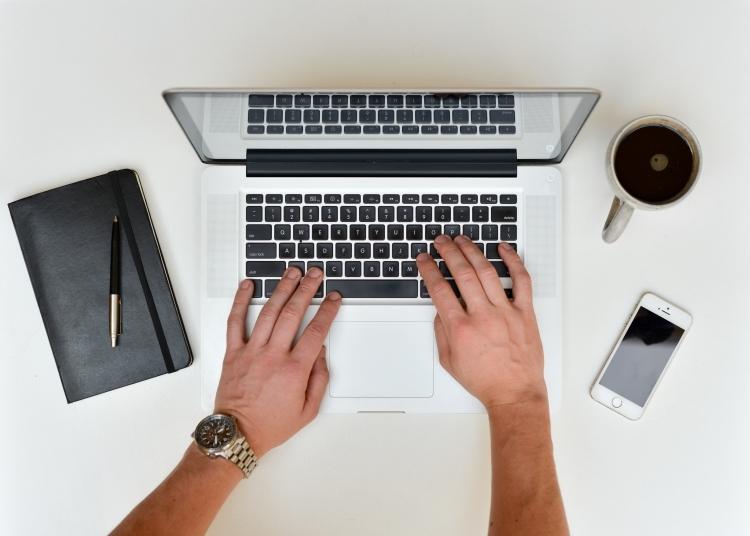 Handen die op een laptop typen