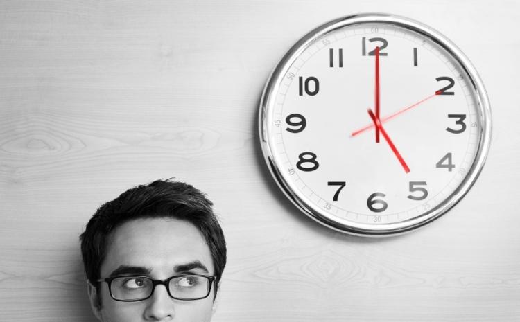 Klok hangt aan de wand en man kijkt naar het tijdstip