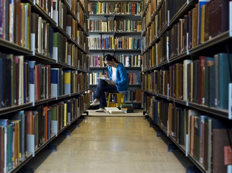 Gang met boekenrekken in een bibliotheek, een vrouw leest een boek