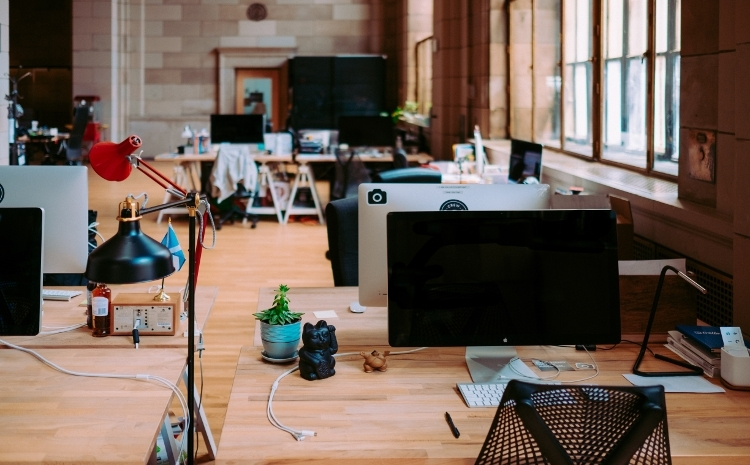 Kantoorruimte met verschillende bureautafels en computers