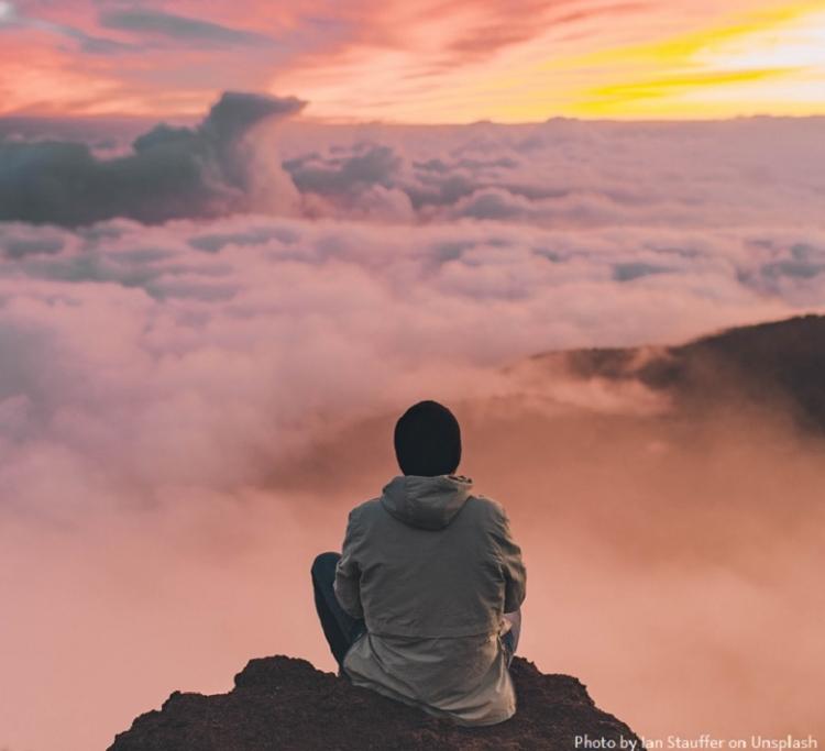 man die vanaf een berg in een zittende positie richting de zonsondergang kijkt