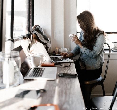 Attractieve vrouw die achter een modern en rommelig bureau zit met een kop koffie en een apple laptop