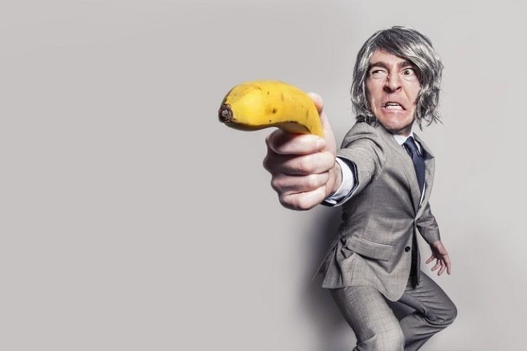 zakenman in een grijs pak met half lange haren die een banaan als een pistool hanteert