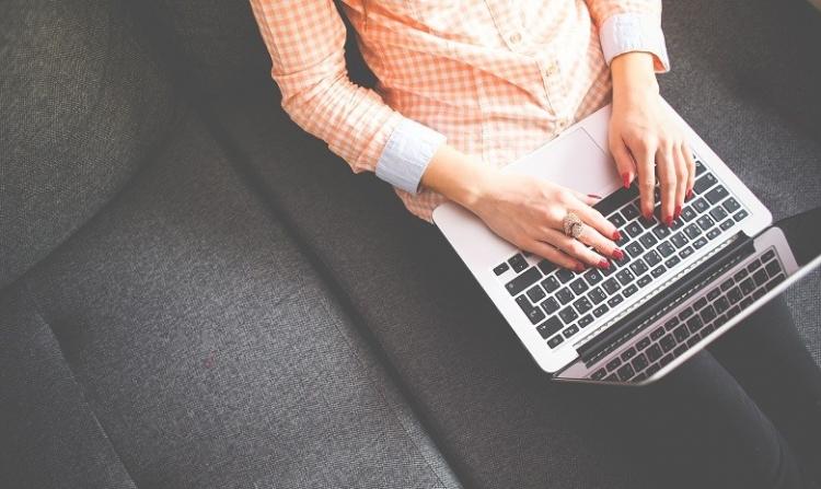 Lichaam en handen van een vrouw die met een laptop op de schoot zit te typen. Ze zit op een zwarte sofa en ze draagt een oranje-rose blouse.