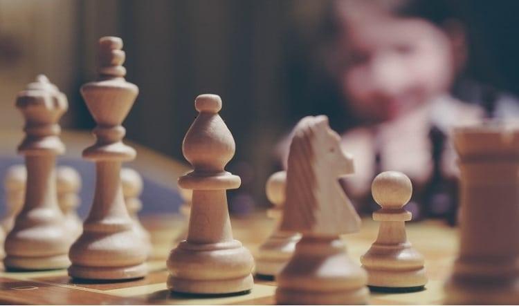 Houten schaakbord van dichtbij gefotografeerd waarbij het paard, de loper, en de koning in focus staan.