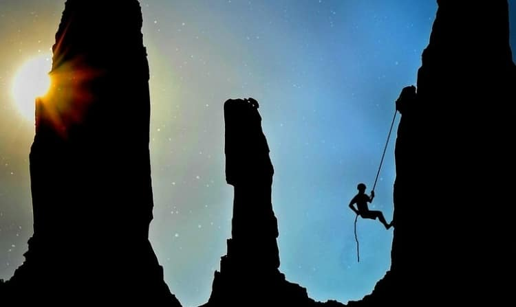 person climbing an Avatar looking mountain with a simple rope in the dark, the sun is shining behind one of the mountains and the main colors are blue, yellow and black. The person climbing the rock is a shadow like figure.