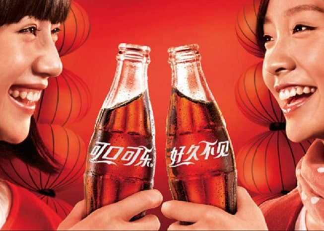 twee Chinese meiden die proosten met een glazen flesje coca cola. De achtergrond is rood en de merknaam coca cola staat in het Chinees op de flesjes geschreven.