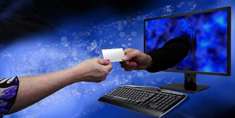 Arm komt uit computermonitor en ontvangt visitekaartje van arm voor monitor